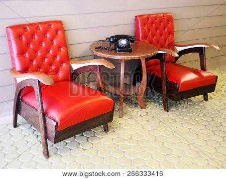 Old Style Living Room With Red Leather Chairs And Antique Telephone Set