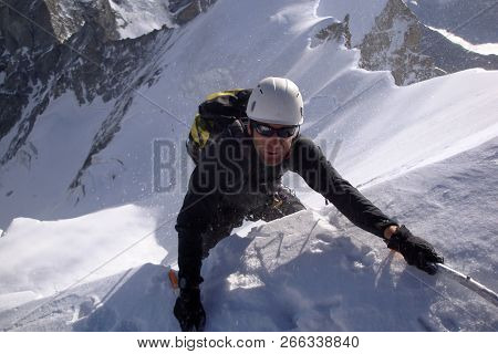 Mountain Climber Reaches The Edge Of A Summit Ridge And Exits A Steep North Face In Windy And Nasty