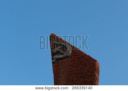Old Communist Monument With The Symbol Of The Ussr Sickle And Hammer Against The Blue Sky, With Copy