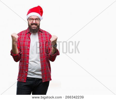 Young caucasian man wearing christmas hat over isolated background celebrating surprised and amazed for success with arms raised and open eyes. Winner concept.