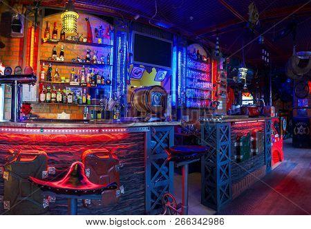 Uzhgorod, Ukraine - Nov 22, 2008: Empty Bar With Bikers Attributes. Neon Lighting And Alcohol Drinks