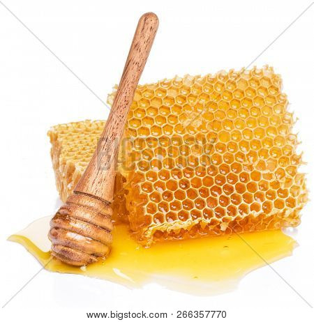 Honeycombs and wooden stick in the honey puddle isolated on white background.