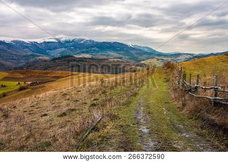Rural Area In November. Wooden Fence By The Country Road. Mighty Ridge With Snowy Peaks In The Dista