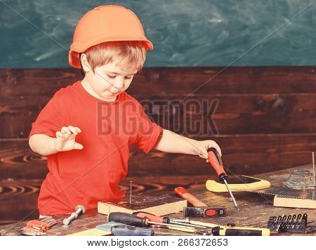 Kid Boy Holds Screwdriver Tool. Handcrafting And Workshop Concept. Child In Helmet Cute Playing As B