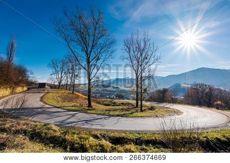 Serpentine In Beautiful Mountainous Countryside. Sunny November Day. Tall Leafless Trees Along The R