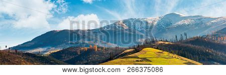 Panorama Of Mountain Ridge With Snowy Peak Above The Hill With Grassy Rural Fields. Wonderful Weathe