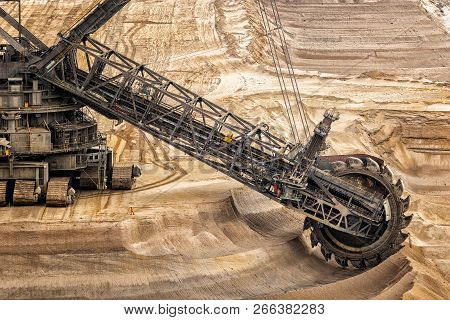 Large Bucket Wheel Excavator Mining Machine At Work In A Brown Coal Open Pit Mine.