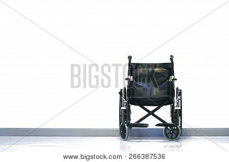 Black And Silver Invalid Wheel Chair In Hospital On White Background With Light.health Care And Disa