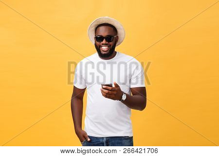 Cheerful African American Man In White Shirt Using Mobile Phone Application. Happy Dark Skinned Hips