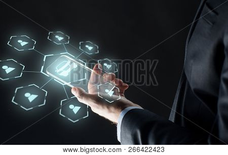 business, transportation and future technology concept - close up of businessman hand with transparent smartphone and virtual car sharing icons over black background,
