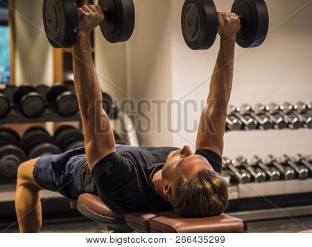 Muscular young man, training pecs on gym bench poster