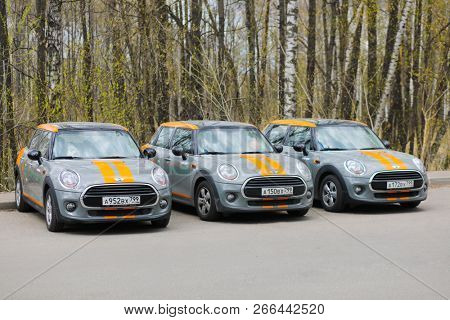 MOSCOW - APR 29, 2018: Three grey BMW mini cars of Moscow carsharing company You drive are near forest, carsharing is system of short-term car rental with per minute payment