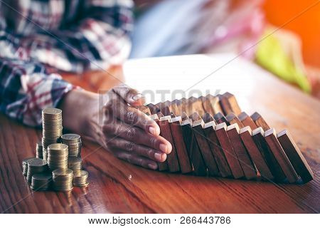 Businesswoman Stops The Domino Effect From Risking Financial Investment, Concept Image Of Investing