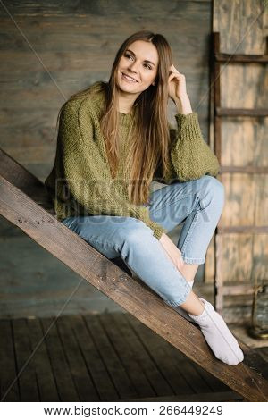 Grunge Fashion: Cute Young Girl Informal Model In Blue Jeans, Dark Knitted Sweater And White Socks S
