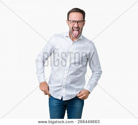 Handsome middle age elegant senior business man wearing glasses over isolated background sticking tongue out happy with funny expression. Emotion concept.