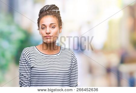 Young braided hair african american girl wearing sweater over isolated background with serious expression on face. Simple and natural looking at the camera.