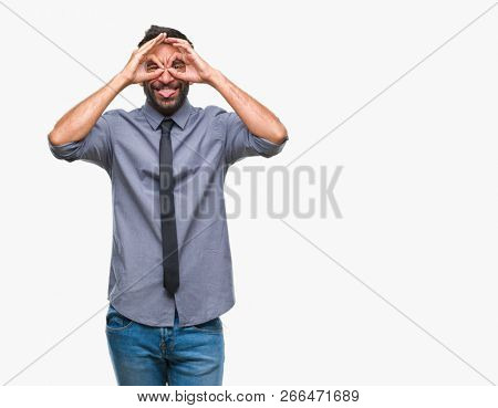 Adult hispanic business man over isolated background doing ok gesture like binoculars sticking tongue out, eyes looking through fingers. Crazy expression.