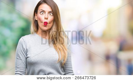 Young beautiful worker business woman over isolated background making fish face with lips, crazy and comical gesture. Funny expression.