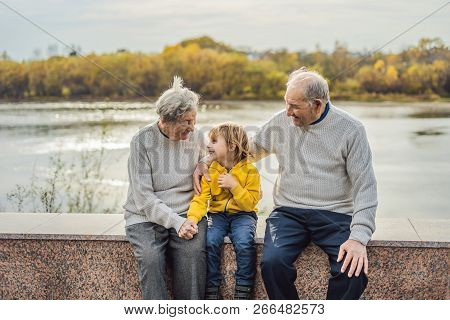 Senior couple with baby grandson in the autumn park. Great-grandmother, great-grandfather and great-grandson poster