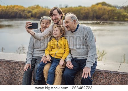Senior couple with with grandson and great-grandson take a selfie in the autumn park. Great-grandmother, great-grandfather and great-grandson poster