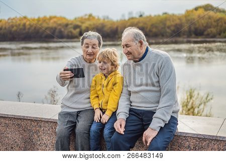Senior couple with great-grandson take a selfie in the autumn park. Great-grandmother, great-grandfather and great-grandson poster