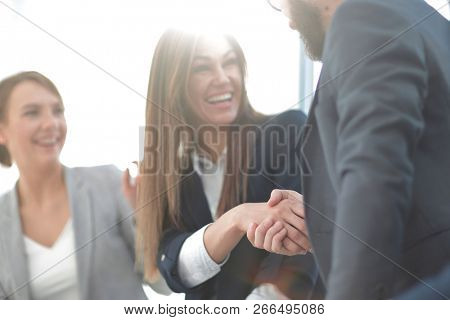 close up.smiling business woman shaking hands with partners