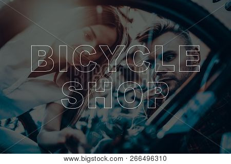 Bicycle Shop. Salesman Showing Bicycle To Customer. Man Looking On The Bike. Man And Woman Sitting.