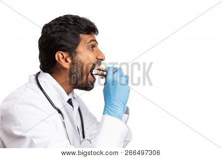 Indian Male Doctor Eating Medicine Blisters As Addiction Or Exaggeration Concept Isolated On White B