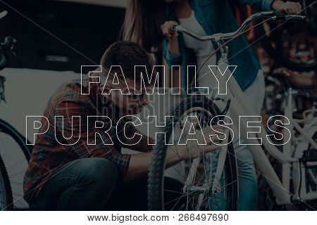Family Purchases. Customers Choosing A Bicycle. Customers Is Couple Of Man And Woman. Man Holding A