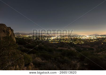 Los Angeles California predawn hilltop San Fernando Valley view.  Burbank, North Hollywood, Griffith Park and the San Gabriel Mountains are in background.