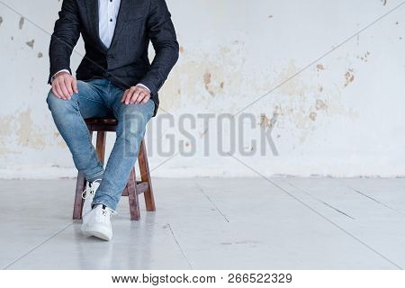Man In Jacket And Jeans Sitting On A Chair. Confident Business Trainer Or Entrepreneur. Smart Casual