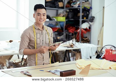 Portrait Of Young Designer Is Going To Start Tailoring And He Looking Sketches On Touchpad While Sta