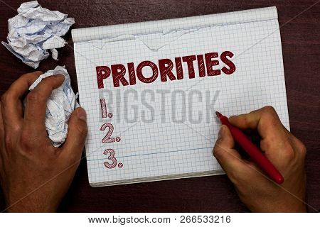 Word writing text Priorities. Business concept for Things that are regarded as more important urgent than others Man holding marker notebook page crumpled papers several tries mistakes. poster