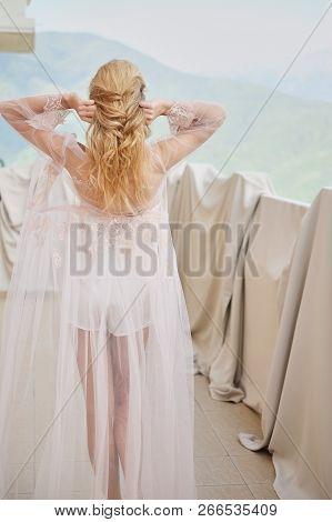 Silhouette Of Young Beautiful Girl Bride In A Peignoir Stands Of The Balcony Overlooking The Mountai