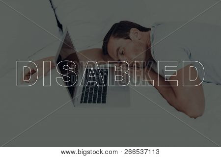 Disabled Man. Man Is Lying On Bed. Man With Closed Eyes. Man Is Sleeping. Laptop Computer Lying On B