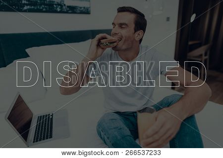Disabled Man. Man Is Sitting On Bed. Laptop Computer Lying On Bed. Man Is Happy And Smiling. Man Eat