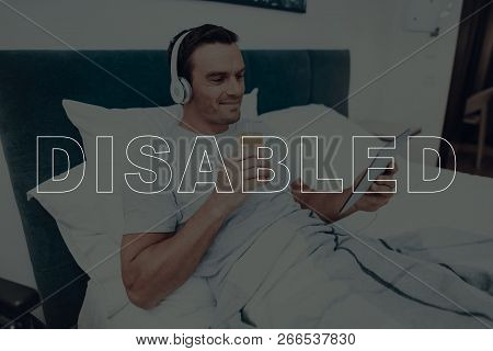 Disabled Man. Man Is Lying In Bed. Man Watching Video On Tablet Pc. Man Wearing Headphones. Man Hold