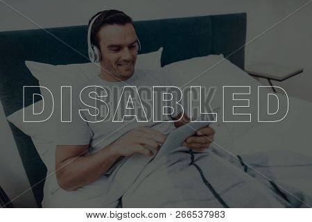 Disabled Man. Man Is Lying In Bed. Man Is Watching Video On Tablet Pc. Man Wearing Headphones. Man I
