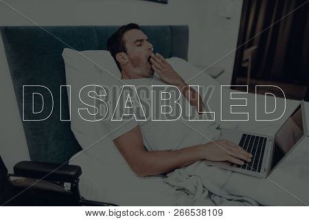 Disabled Man. Man Is Lying In Bed. Man Using A Laptop Computer. Man Typing On Laptop. Man Is Yawning