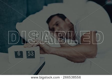 Disabled Man. Man Is Lying In Bed. Man Woke Up. Clock On Table Near Bed. 6:53 Time On Clock. Man Dis