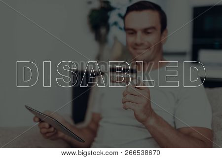 Disabled Man. Man Is Sitting On Sofa. Man Holding A Credit Card. Man Using Tablet Pc. Man Doing Shop