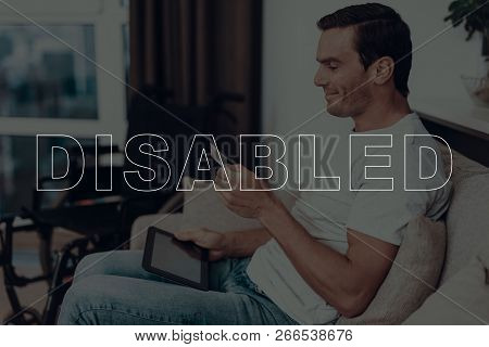 Disabled Man. Man Is Sitting On Sofa. Wheelchair On Background Of Man. Man Holding A Credit Card. Ma