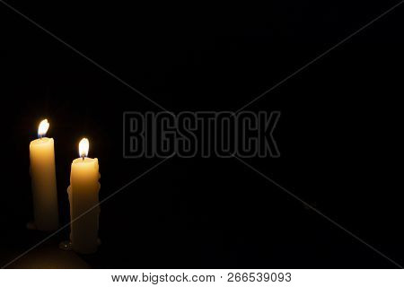 Two Candles On Dark Background. Lighting Candles On Black. Yellow Wax Candle With Warm Flame. In Mem