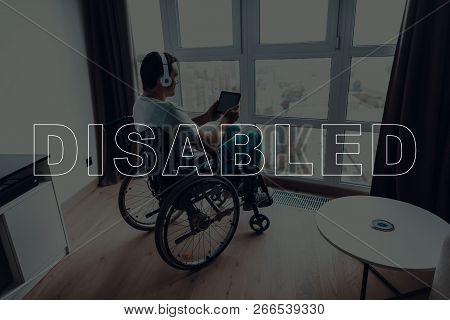 Disabled Man In A Wheelchair. Man Sits In Front Of Window. Large Panoramic Window. Man Watching A Vi