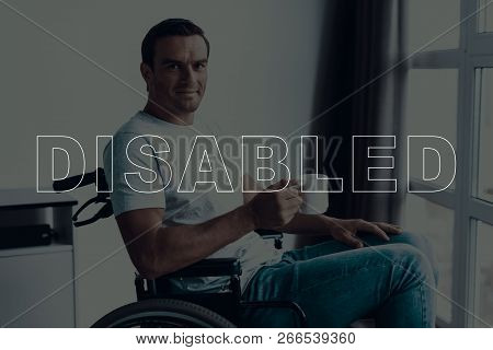Disabled Man In A Wheelchair. Man Sits In Front Of Window. Large Panoramic Window. Man Looks Into Ca