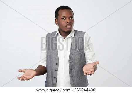 Young african man in blue shirt being at a loss, showing helpless gesture with arm and hand poster