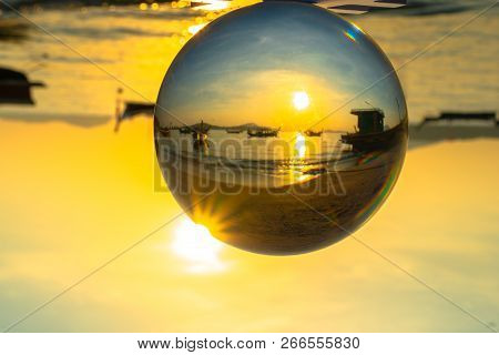 crystal glass ball sphere reveals sunrise seascape with spherical perspective on the beach in Phuket