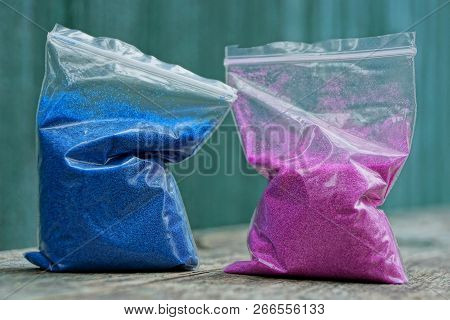 Two Plastic Bags With Blue And Red Sand On The Table