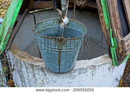 One Gray Metal Bucket Of Water Stands On An Open Well In The Street