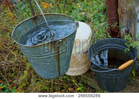 Three Buckets Of Water Are On The Street In The Green Grass